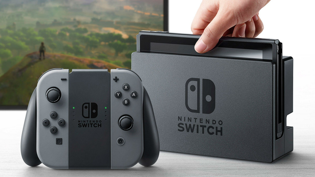 NintyPricer - This is the Nintendo Switch console with a hand for size comparison.